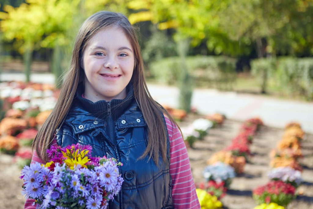 Girl with Down syndrome holding flowers in park