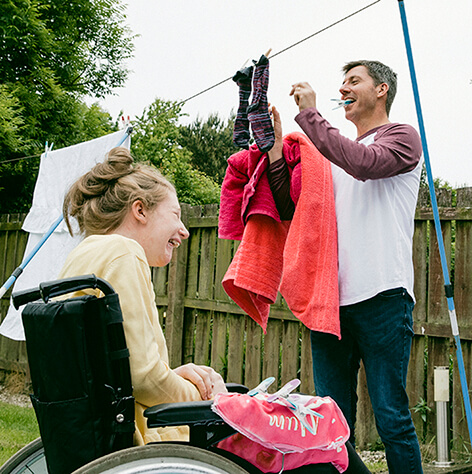 Father hanging clothes on the line with his daughter in her wheelchair.