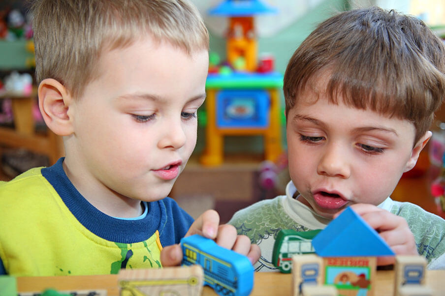 Two young boys playing with blocks at kindergarten.