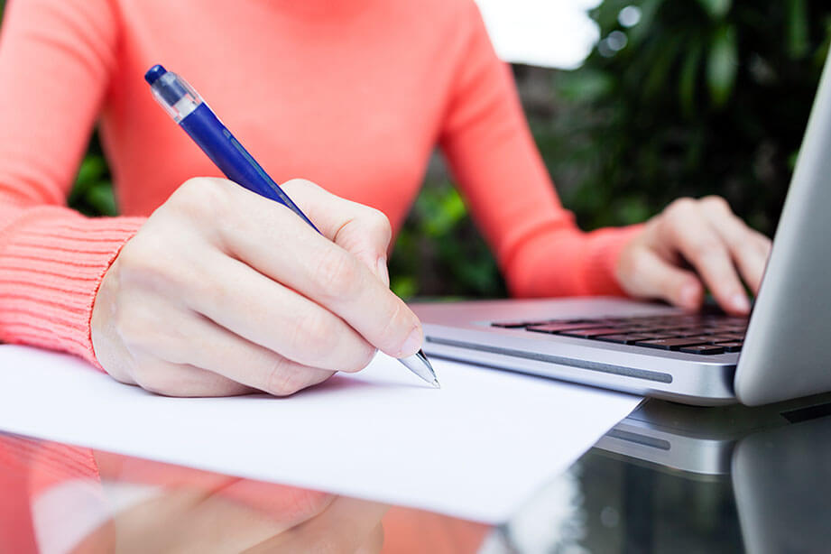 Woman's hand writing notes and using a laptop.