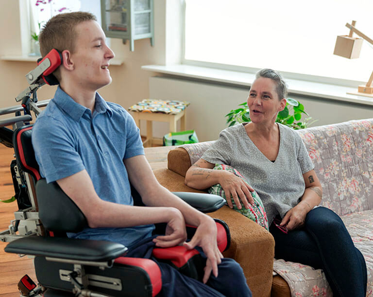 Teenage boy in a wheelchair talking to his mother at home.