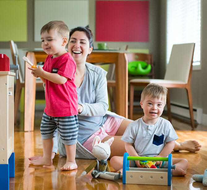 Toddler boy with Down syndrome playing with his mother and brother at home.