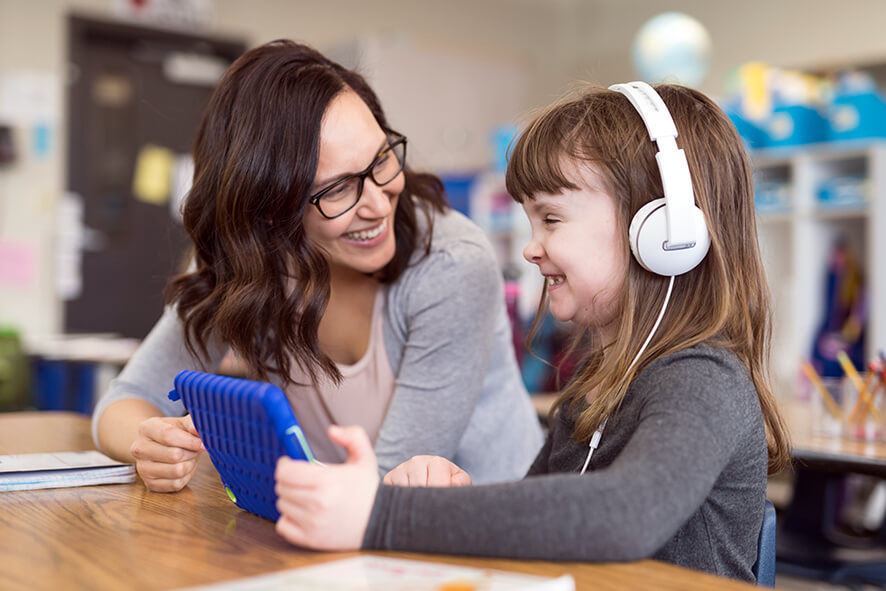 Female teacher smiling at young female student who is wearing headphones and using a digital tablet.