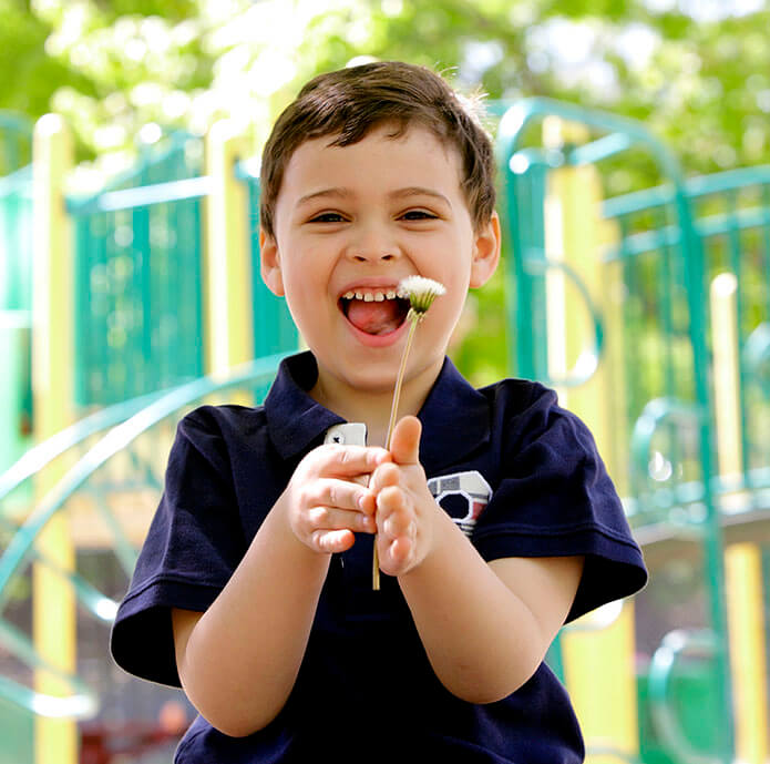 Young boy with autism laughing and holding a dandelion at the park.