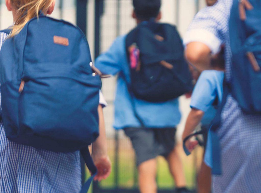 School children wearing backpacks walking into school.