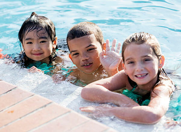 Two girls and a boy in a pool holding on to the wall, the boy in the middle is waving hello.