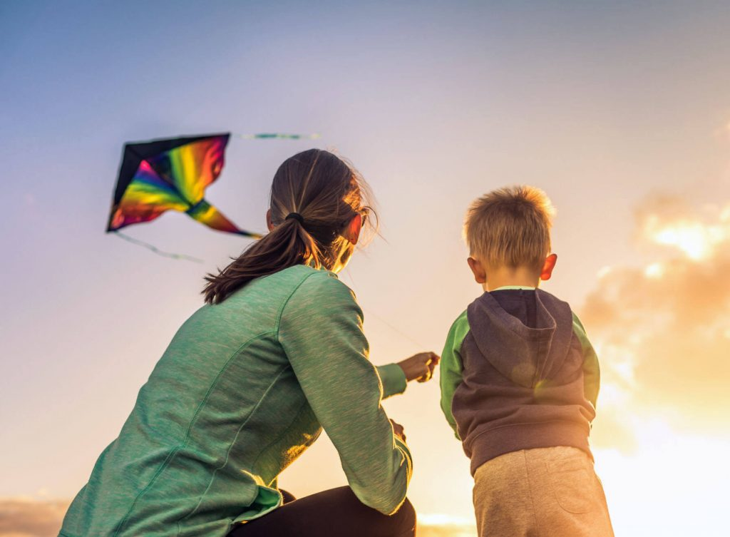 A mother and young son flying a rainbow coloured kite at sunset.