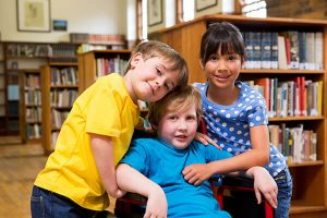 Young boy in a wheelchair with two friends who have their arms around him in the library.