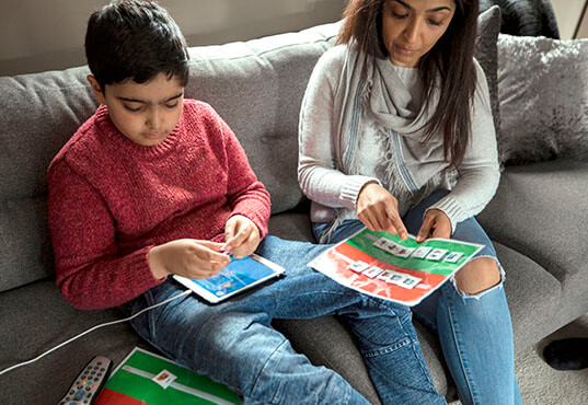 A mother sitting next to her son with autism on the couch at home, helping him to use a picture communiction tool and digital tablet.