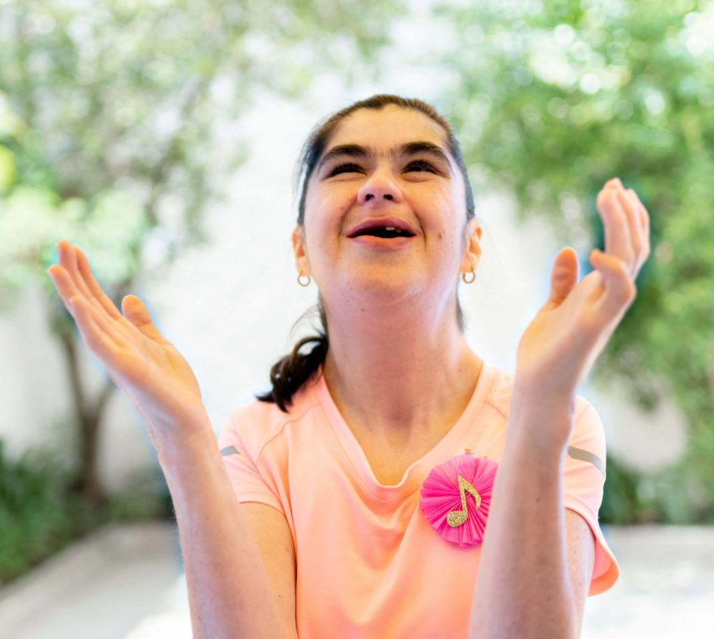 A teenage girl with disability singing and clapping outside.
