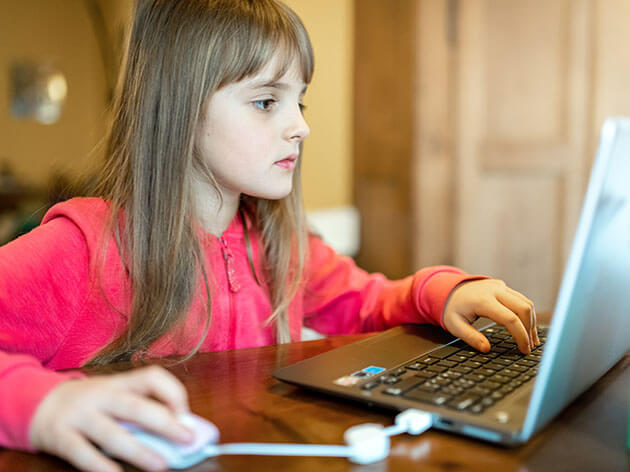Eight year old girl learning from home using a laptop computer with a mouse.
