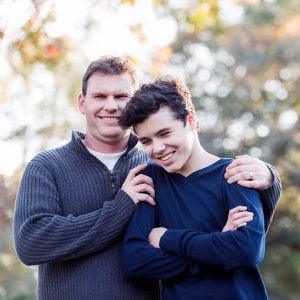 Father and teenage boy standing outdoors together.