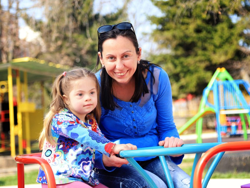 Mother with daughter who has Down syndrome having fun on a whizzy-dizz at the playground.
