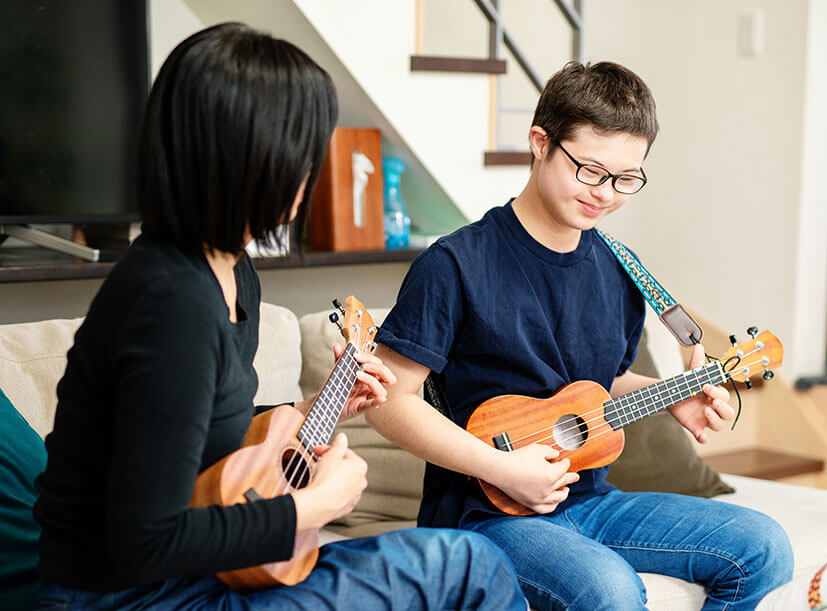 Teenage boy with Down syndrome sitting at home on the couch with a Support Worker as they both play the ukele.Support Worker