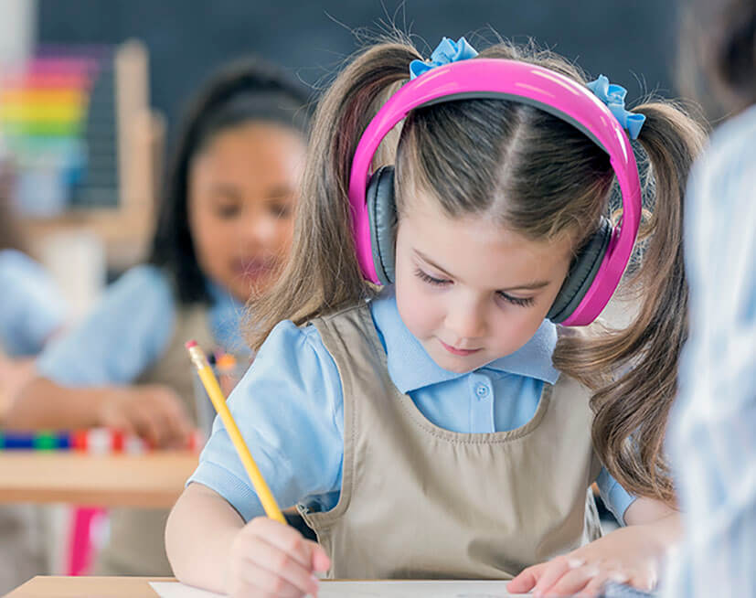 Young schoolgirl wearing headphones while writing at her desk at school.