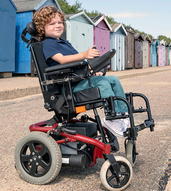 Young boy in power wheelchair by beach huts at the beach.