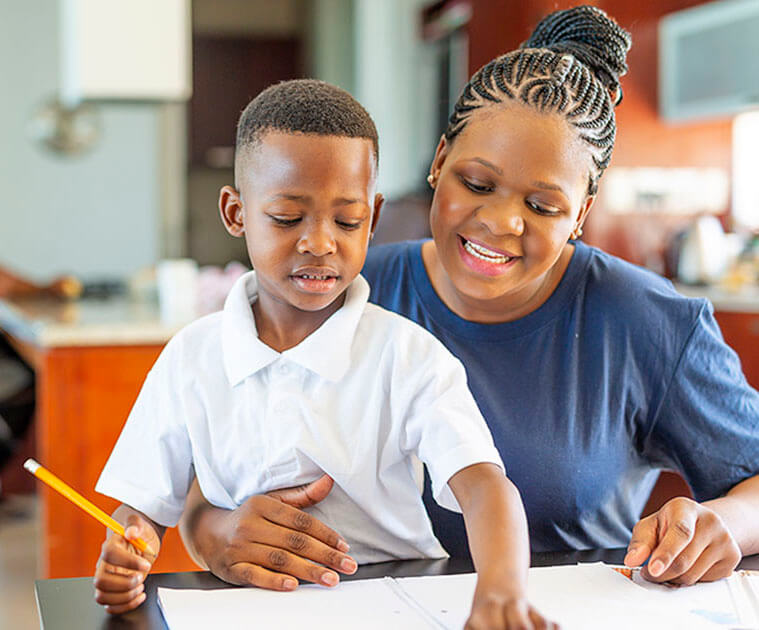 A mother helping her son to do homework at the kitchen table.