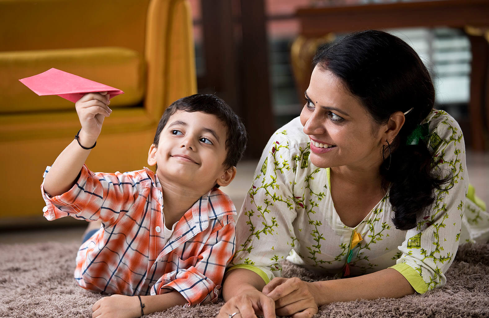 Mother and son playing with paper airplane.