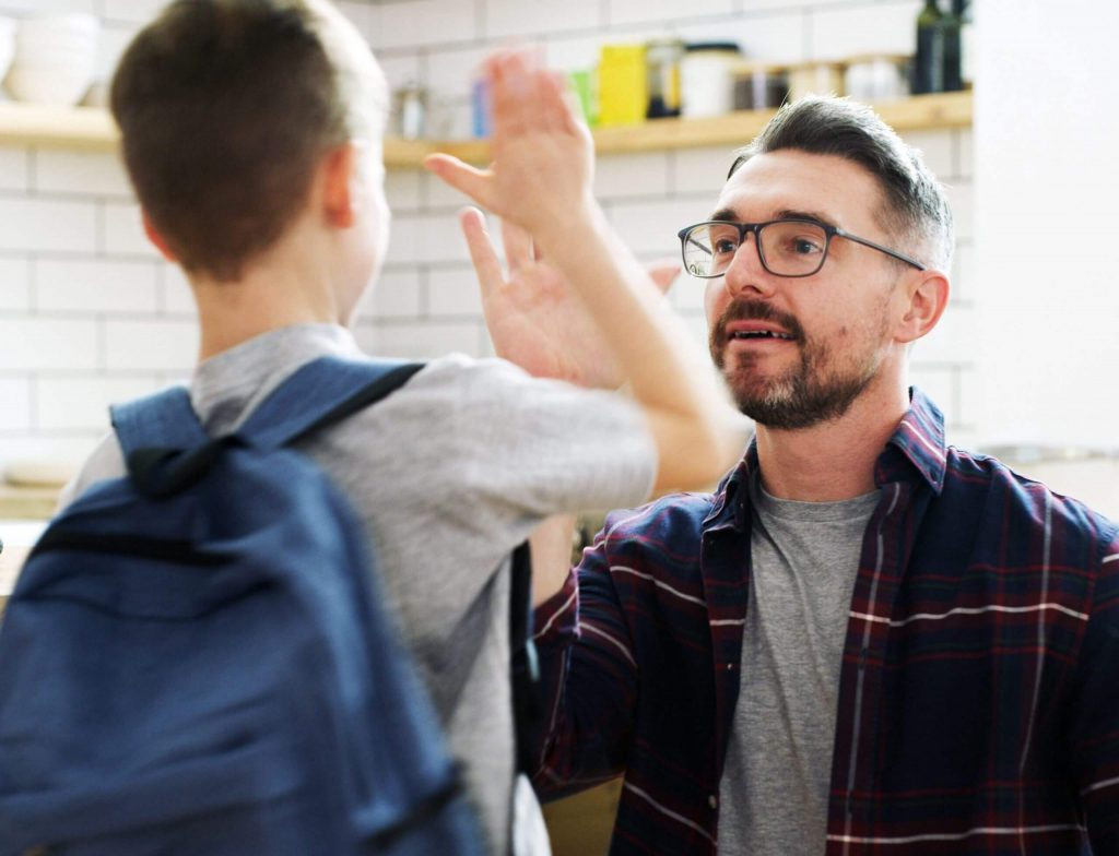 A dad giving his son a high five before he goes off to school.