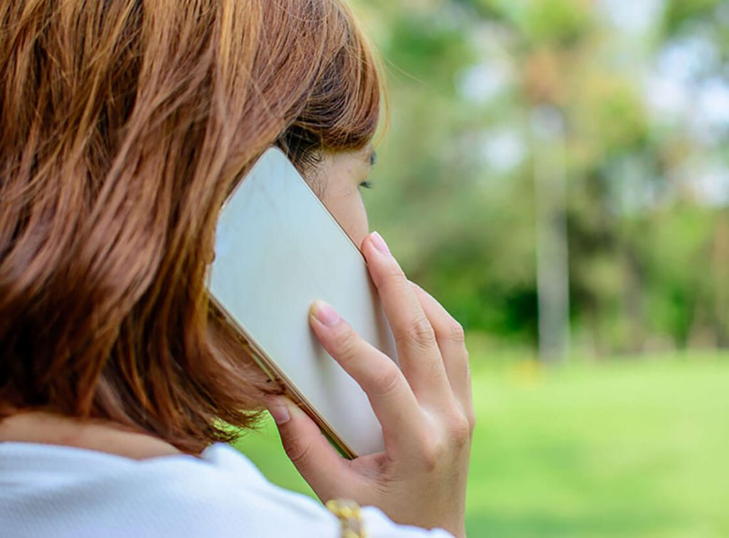A woman talking on mobile phone, she is standing outside looking into the distance, only the side of her face and hair is in view.