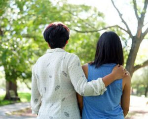Back view of mother and daughter standing together outside in a park.