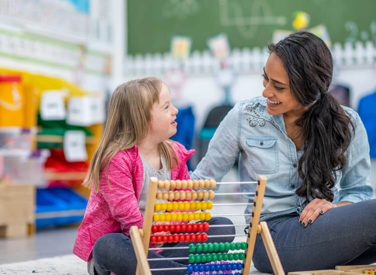 Educator sitting on the floor talking to a young girl with Down syndrome who is playing with an abacus.