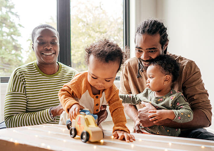 A mum and dad playing cars with their two young children.