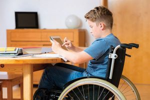 Teenage boy in a wheelchair sitting at the kitchen table using a computer tablet to do school work.