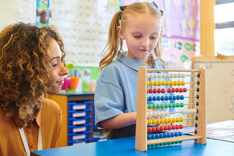 A young female student moves beads on an abacus as her female teacher watches on.