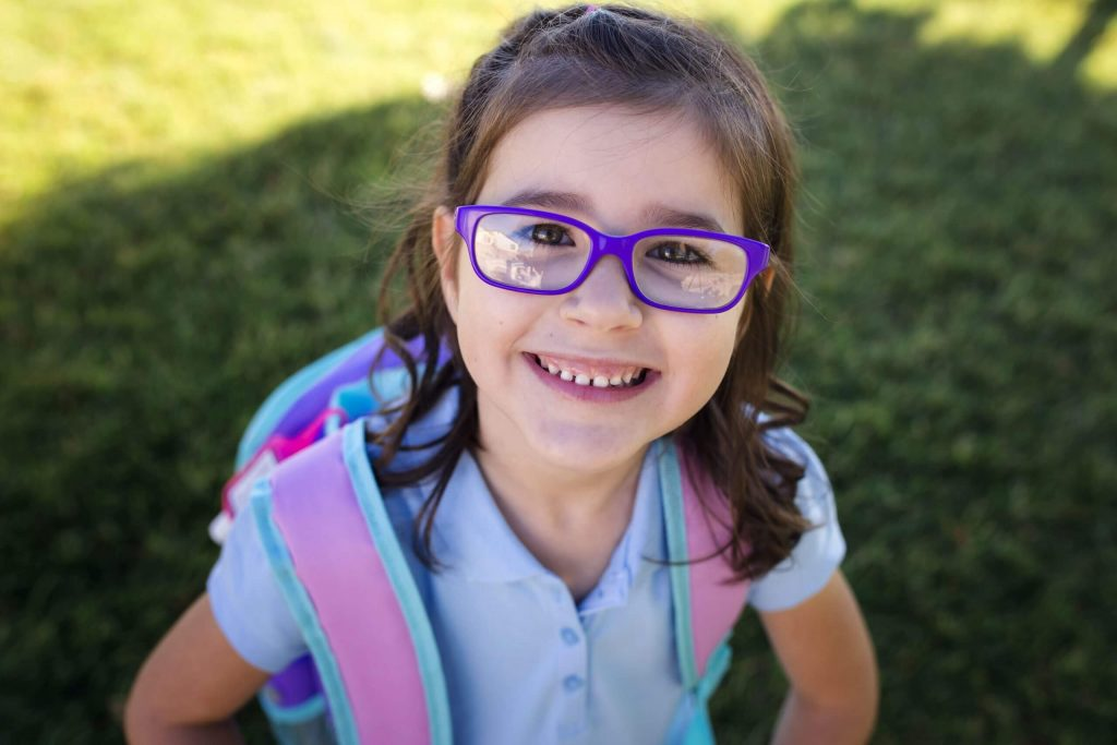 A smiling young girl with purple glasses wearing school uniform and a backpack.