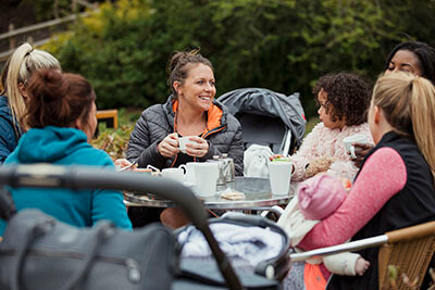 A group of mums sitting at a table in the park having a coffee and a chat.