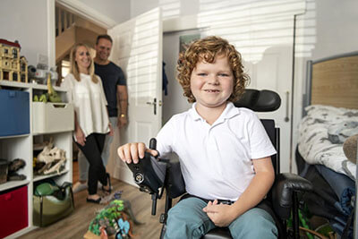 Boy with muscular dystrophy in his bedroom using his powered wheelchair as his mum and dad smiling and watching in the background.